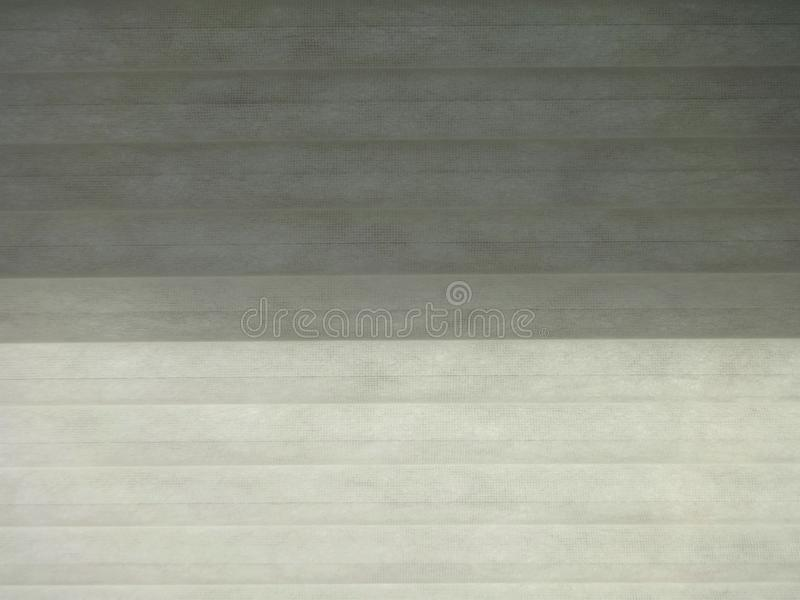 Window covering showing light and shades. Textured horizontal window coverings showing light and shades in a room stock photo