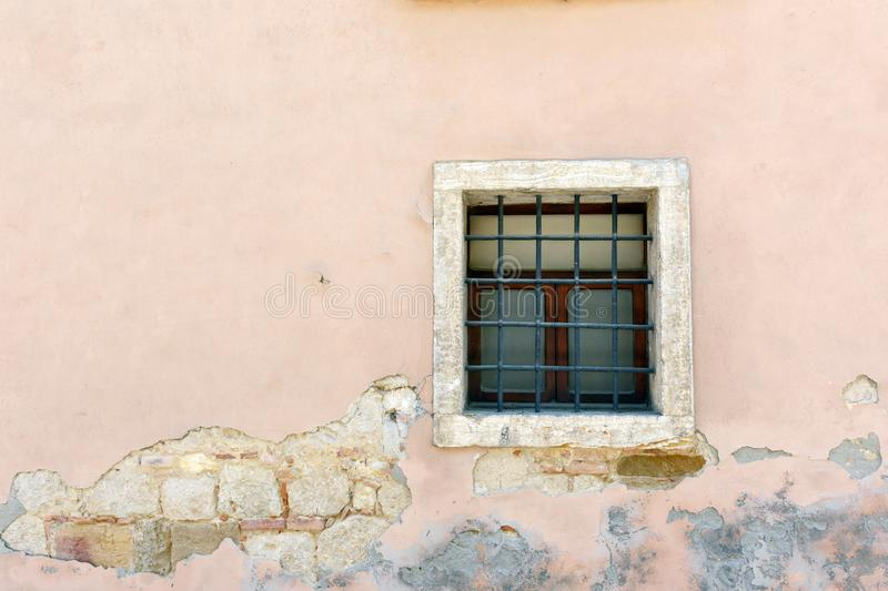 Window in a cracked wall; in horizontal orientation. Color image of a window in an ancient, cracked wall; in horizontal orientation stock photo