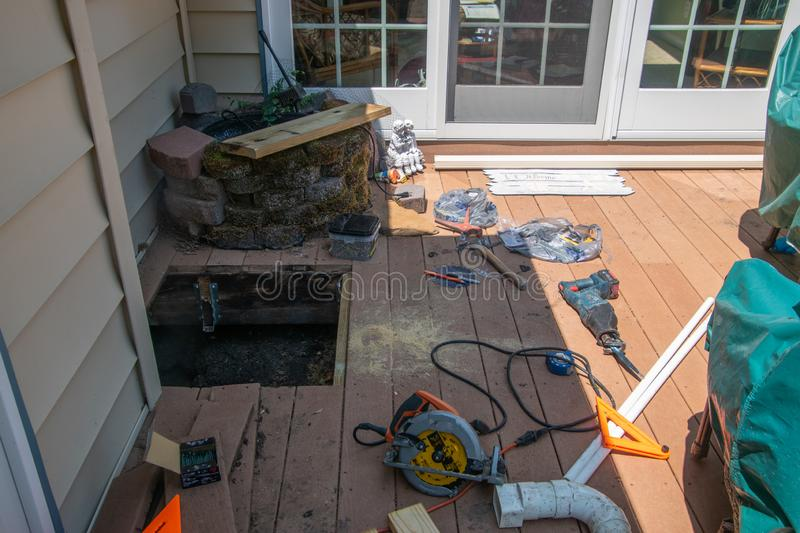 A window cut into brown wooden deck in order to repair a drainage problem under the deck. There are various power tools on the. stock photography