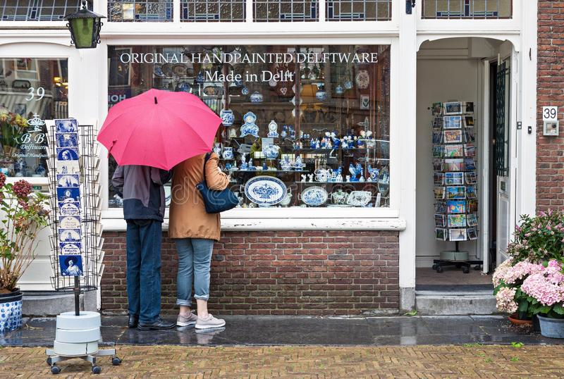 Window display of traditional Dutch handpainted pottery shop in. Delft, Netherlands - August 25, 2018: Two tourists with red umbrella looking at window display royalty free stock image