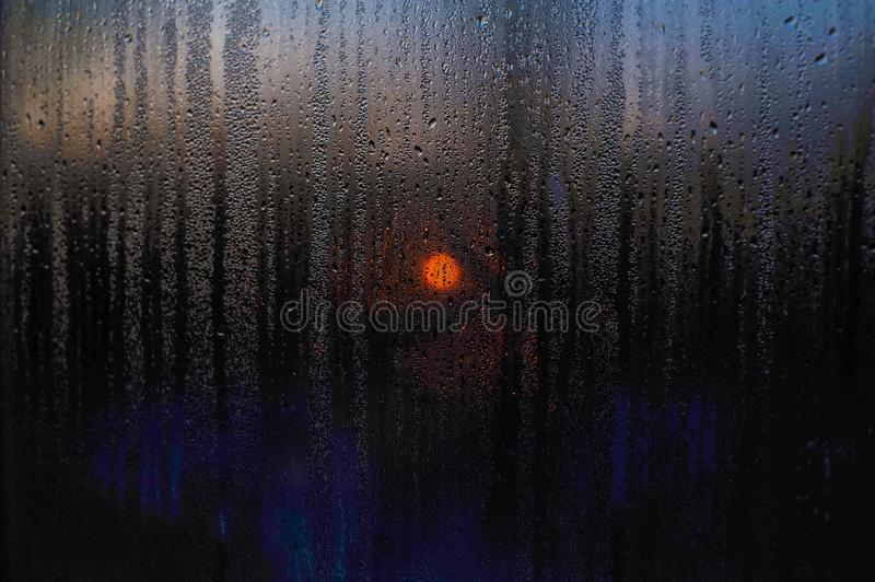 Window drops of rain sunset of the sun scenes landscape. Sunset on a background of rain through a window of a drop of rain on a glass close up. The concept of stock image