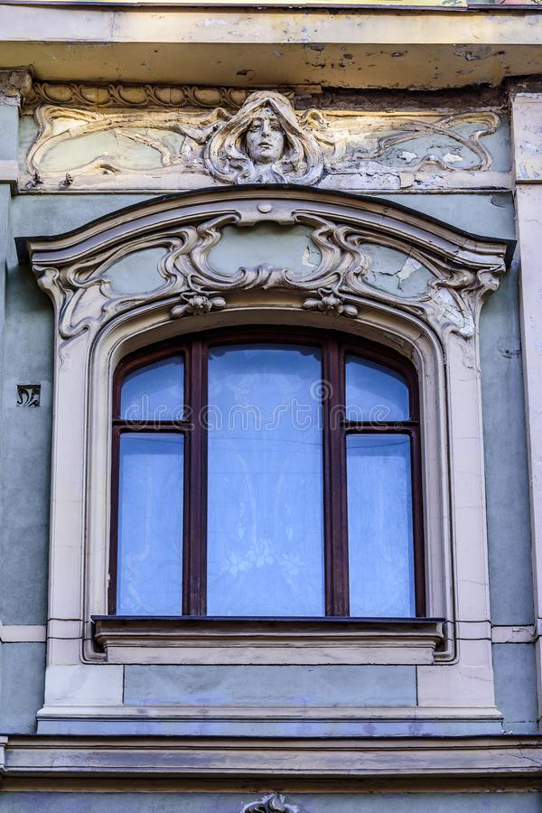 Window, female mask, stucco on the facade of a very old building in the Empire style. City of Moscow, Petrovsky lane 8, Russia.  stock photography