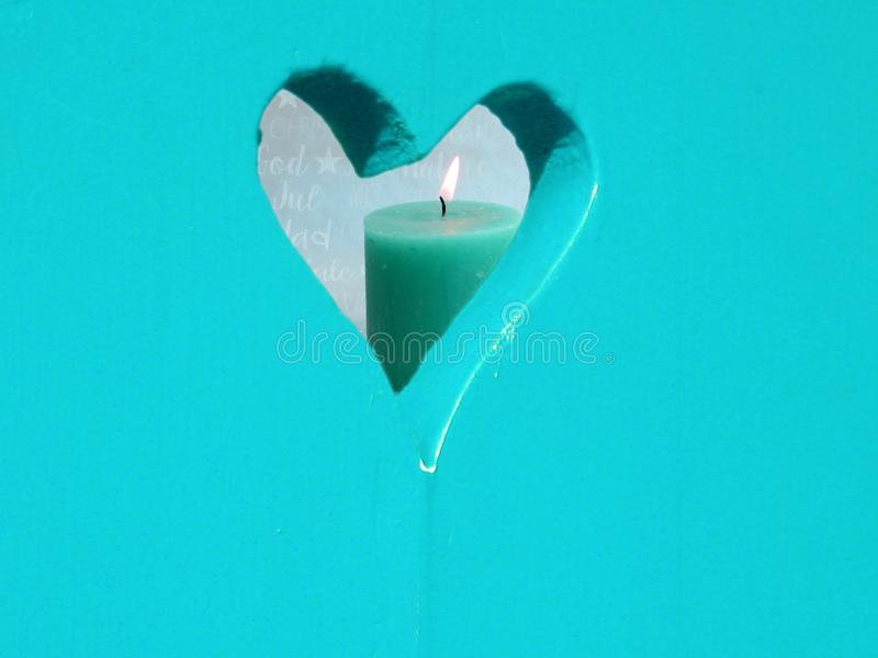 Window in the form of a heart with a candle in front of a christmas background stock images