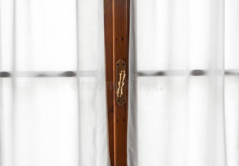 Window frame detail with vintage handle and white curtains stock image