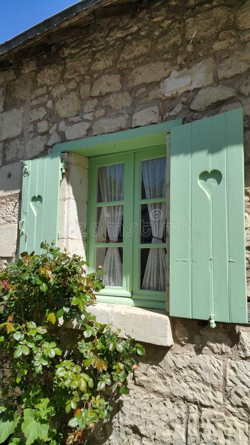 Window with green frames and wooden shutters and lace curtains stock image