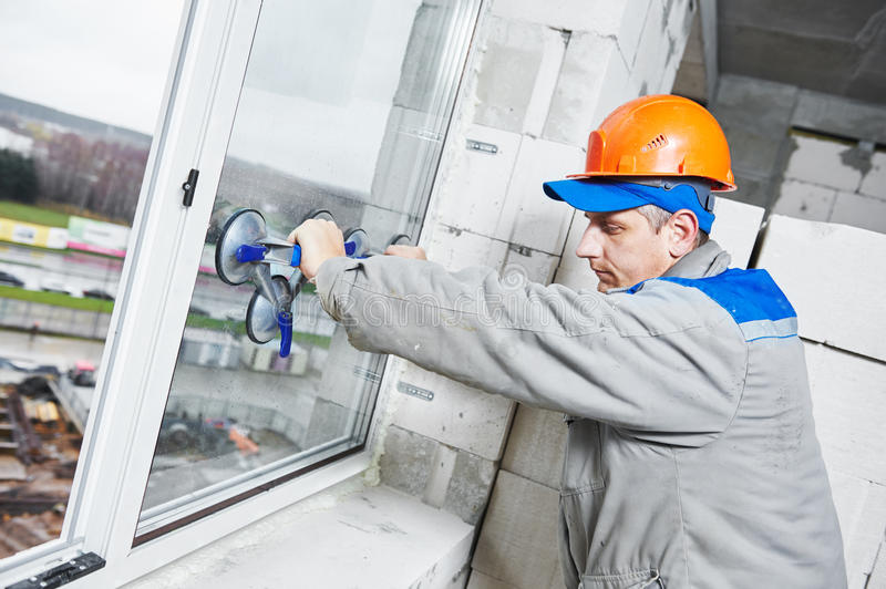 Window installation or glazing. Male industrial builder worker at window installation in building construction site royalty free stock image