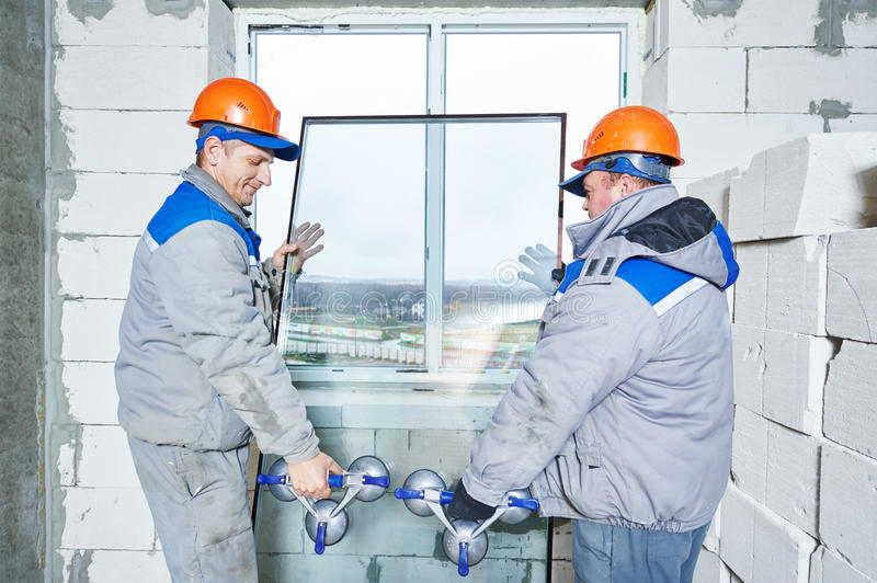Window installation or glazing. Male industrial builders worker at window installation in building construction site stock photos