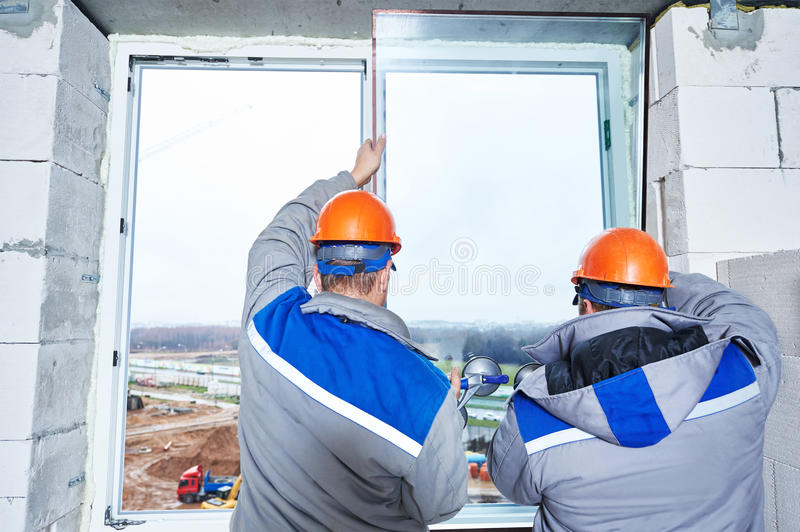 Window installation or glazing. Male industrial builders worker at window installation in building construction site royalty free stock photos