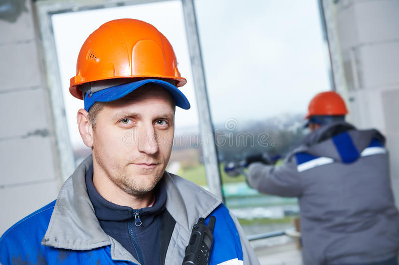 Window installation or glazing. Portrait of male industrial builder worker at window installation in building construction site stock photos