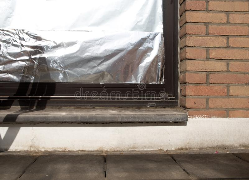 Window insulated with aluminium foil to protect house against heat wave stock photography