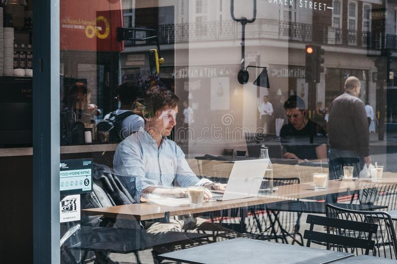 Through the window of men working on laptops inside a cafe in Marylebone, London, UK. London, UK - July 18, 2019: Through the window of men working on laptops stock photography