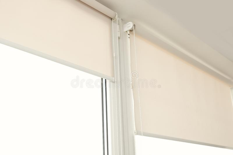 Window with modern roll blinds in room. Closeup stock photography