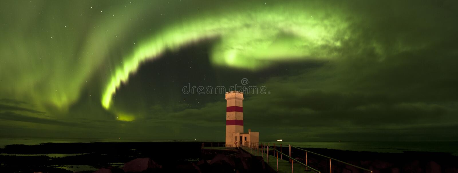 Window in the night sky over lighthouse in Iceland under northern lights stock image