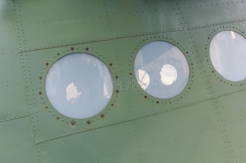 Window in old airplane, aluminum background detail of a military aircraft stock photography