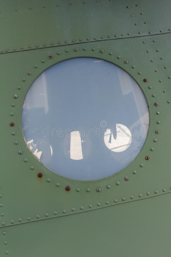 Window in old airplane, aluminum background detail of a military aircraft stock image