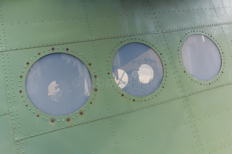 Window in old airplane, aluminum background detail of a military aircraft. Window in old airplane, aluminum background detail of a military porthole aircraft royalty free stock photo