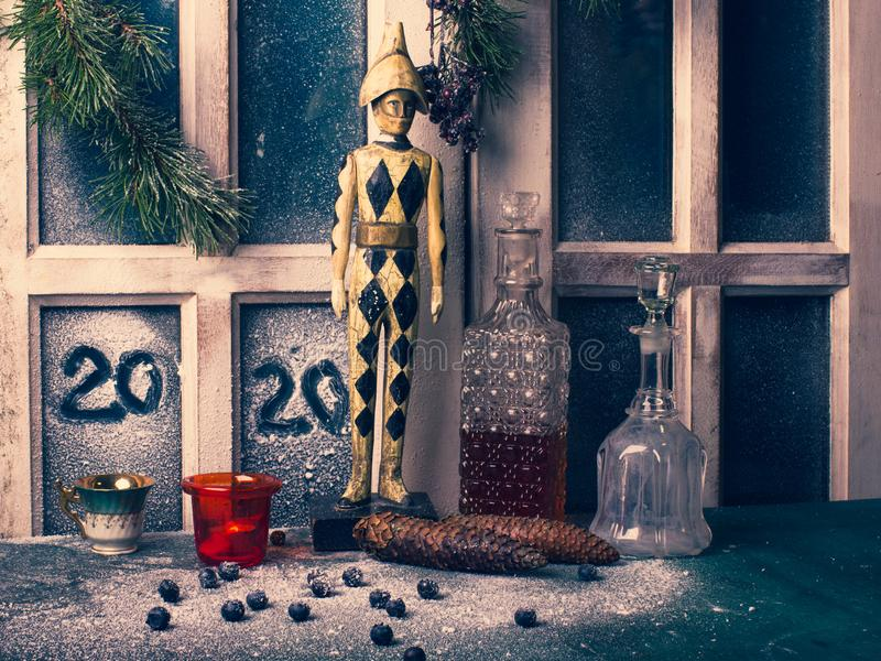 Window of an old cottage. 2020 numbers are drawn by hand on a frozen window decorated with branches, cones, arlequino sculpture stock image