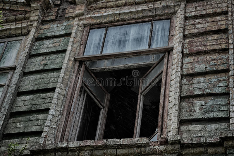 The window of the old creepy abandoned scary house in which lives a Ghost and a murder stock photo