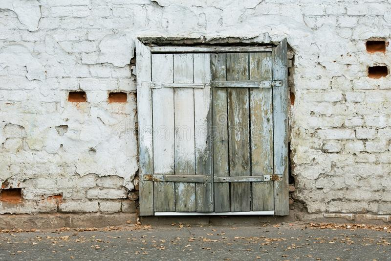 The window of the old house is covered with wooden shutters. At street level royalty free stock photography