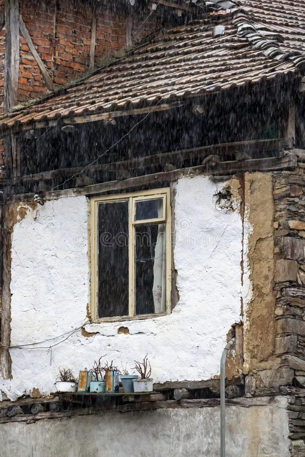 Window of an old poor house with plant pots under the rain, village of Pirin in Pirin Mountains, Bulgaria, architectural detail royalty free stock photography