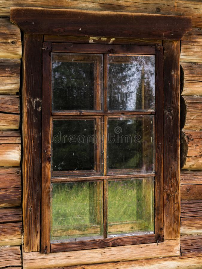 Window in an old rustic log house with the reflection of meadow. Elements of an old rustic house made of wooden logs stock photo