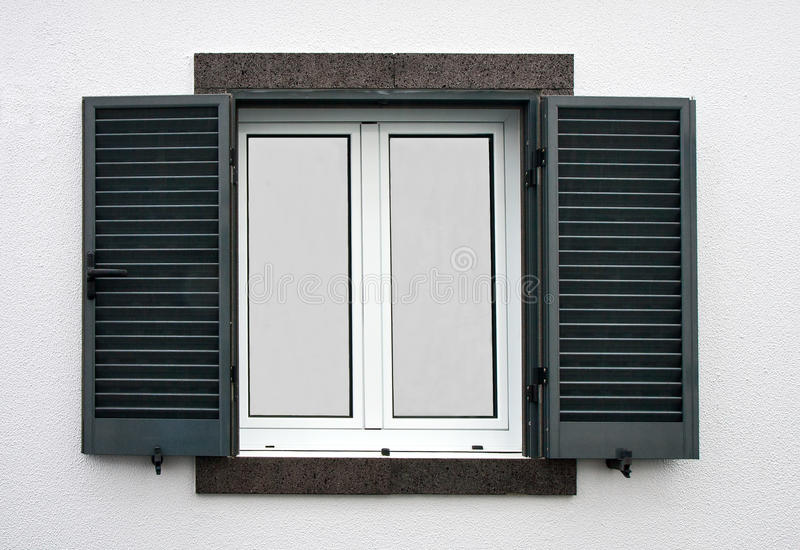 Window with open shutters. On a white stone wall royalty free stock images