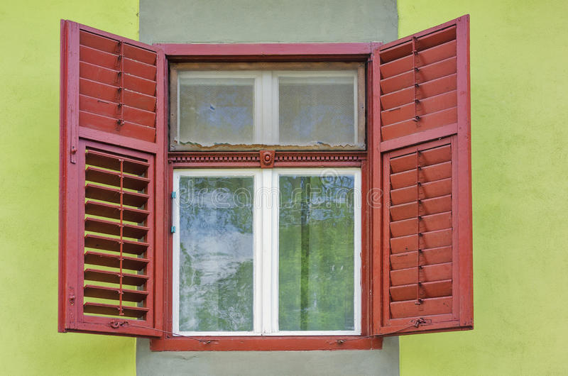 Window with open shutters. On a green wall royalty free stock photo