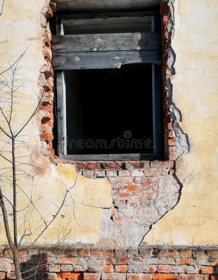 Window opening without a window in the wall with loose stucco in an old building. sunny day royalty free stock photo