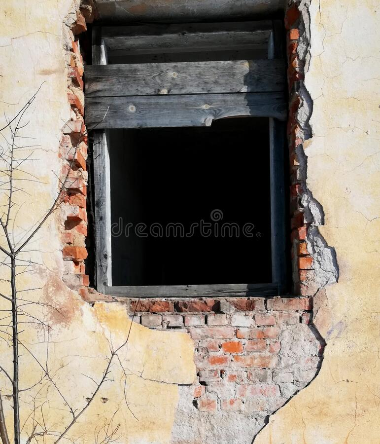 Window opening without a window in the wall with loose stucco in an old building. sunny day royalty free stock images