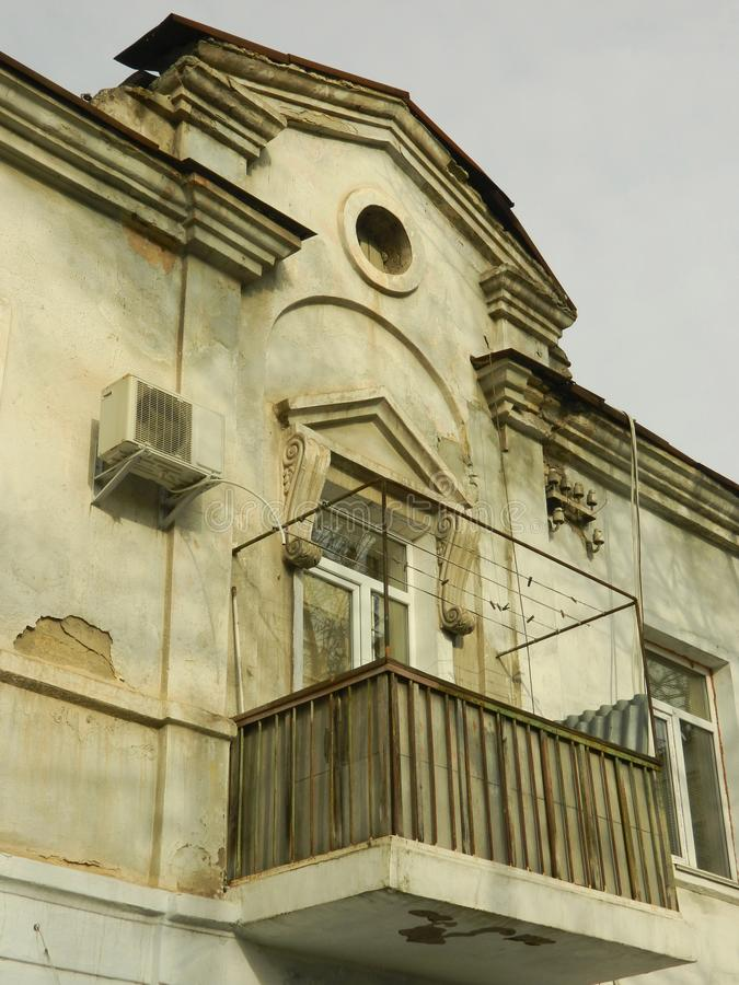 Window with a pediment and oculus. A balcony and window decorated with a pediment and oculus of an old building on Velyka Morska Street in the historical part of royalty free stock photo