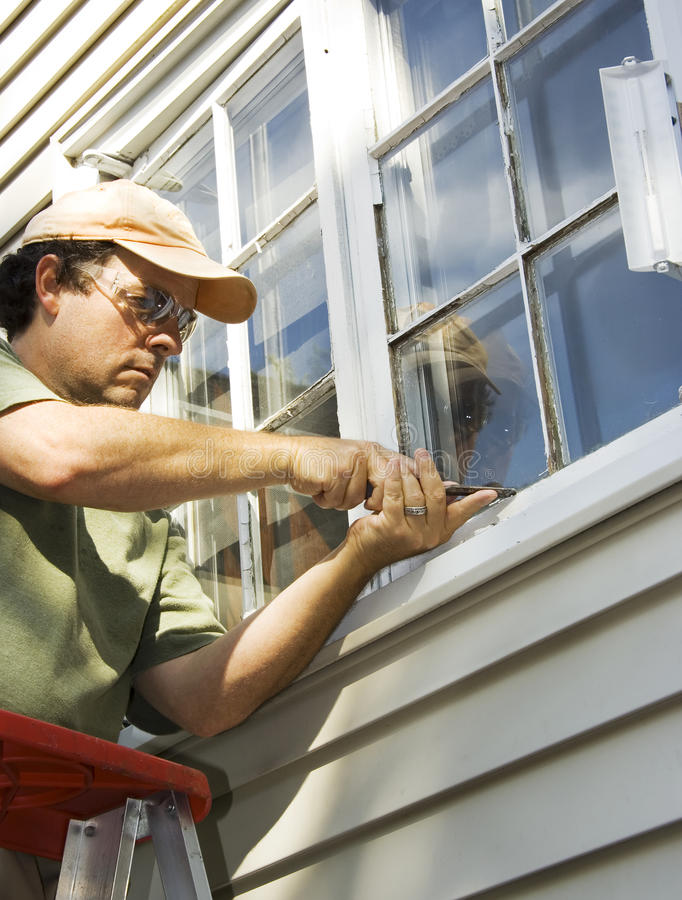 Window Repair. Man working on a windw to remove old glazing with a chisel stock photos