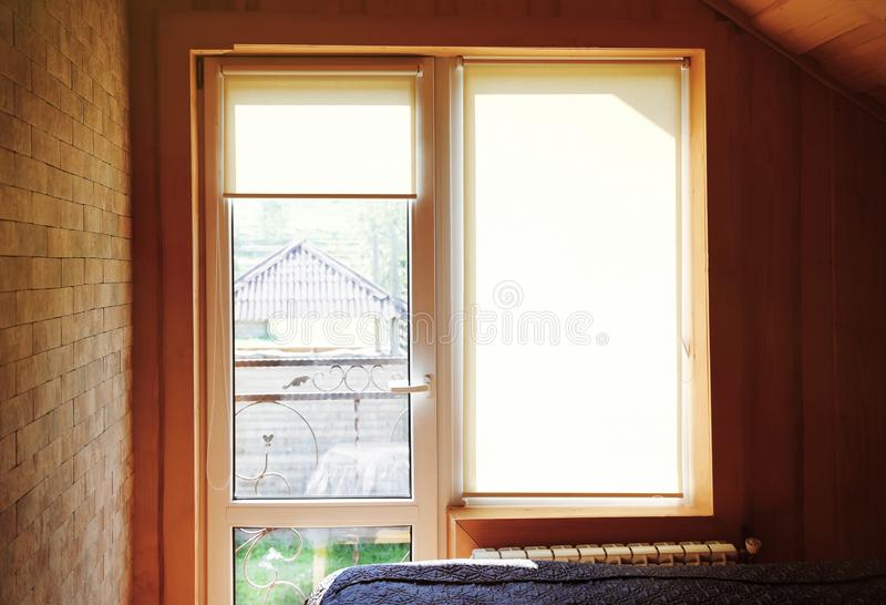 Window with roller curtains in bedroom. On sunny day royalty free stock photography