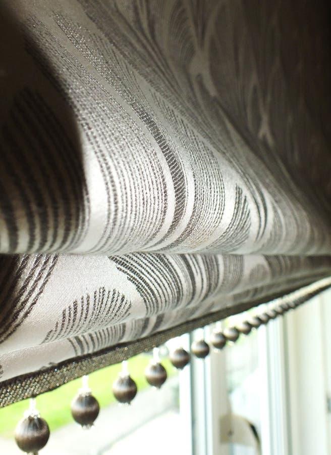 Window Roman blind/grey blind. Roman blind, interior design styling. Pom-pom trim royalty free stock images