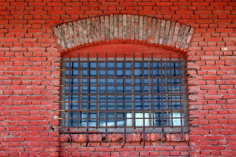 Window with safety wire protection and strong metal bars mounted on old red brick wall. Window with safety wire protection and strong metal bars in shape of net stock image