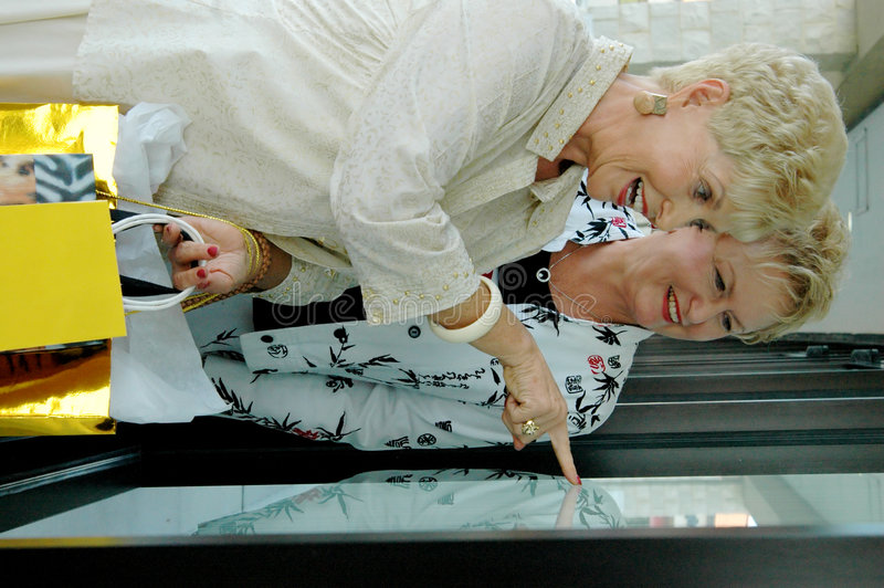 Window shopping. Two senior women looking in shop window