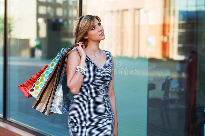 Young woman with shopping bags at the mall window royalty free stock image