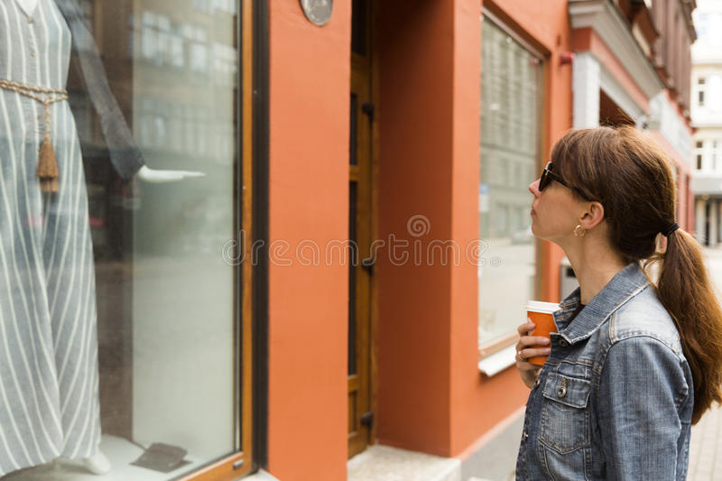 Window shopping concept. Young woman looking at dress in a shop window. stock photo