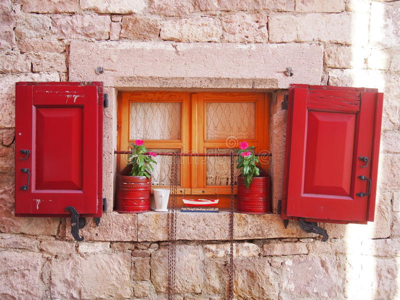 Window shutter. Old wooden window shutter decorated with flower pots from Cunda island Ayvalik royalty free stock photography