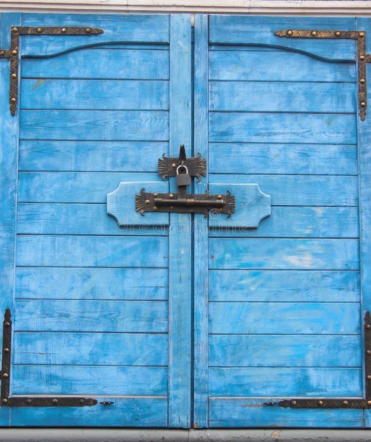 Window shutters. Antique blue wooden window shutters stock images