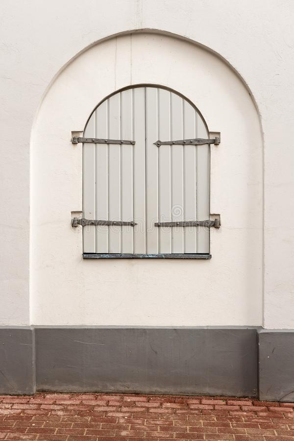 Window with shutters in the wall of an old building.  stock images