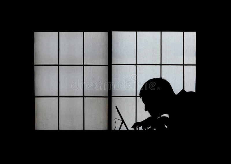 Window silhouette of a creepy computer hacker hunched over a laptop late at night royalty free stock photo
