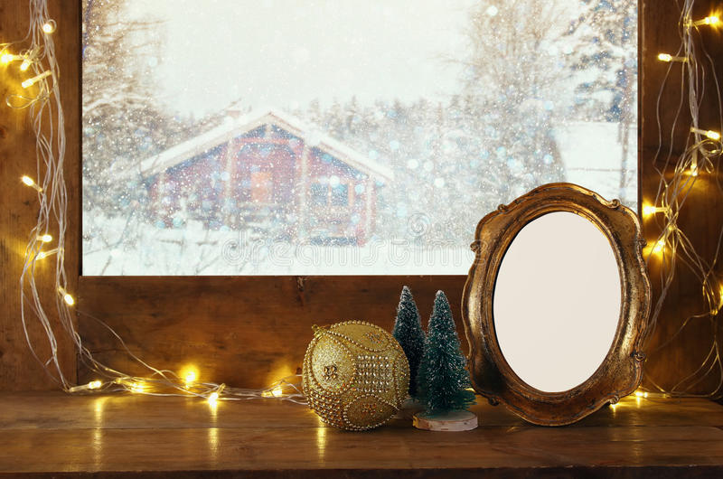 window sill with christmas lights and empty vintage frame stock photos