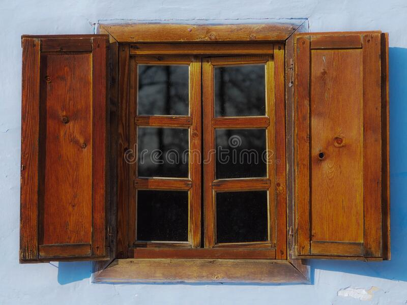 Window with six panes and wooden shades on an old village house painted in light blue. wood in natural brown colour. royalty free stock photo