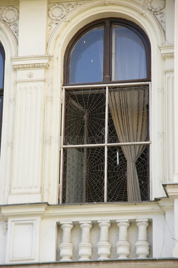 Window with spider webs. Window with cobwebs, and curtains, photo taken in Budapest royalty free stock photography
