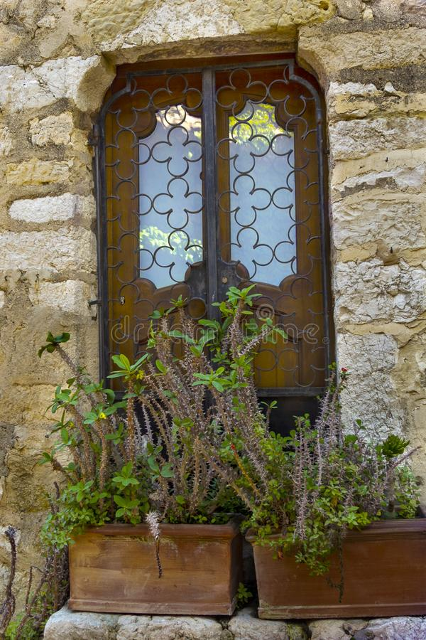 Window in the stone wall. Eze village at french Riviera coast Provence, France. Window in the stone wall in medieval Eze village at french Riviera coast near stock image