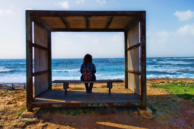 Window to the sea. Young woman sitting on a bench in a box on a sunny day looking at the sea royalty free stock image