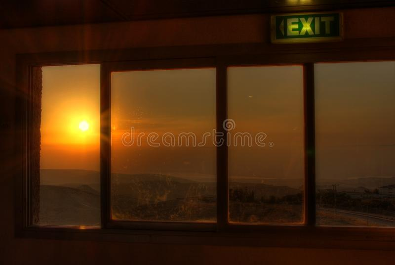 Window to the Sunrise over the Desert with symbolic exit Sign royalty free stock photo