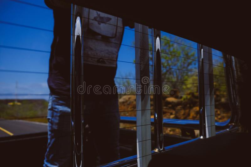 Window of a truck with metal bars and a male standing in the back royalty free stock images