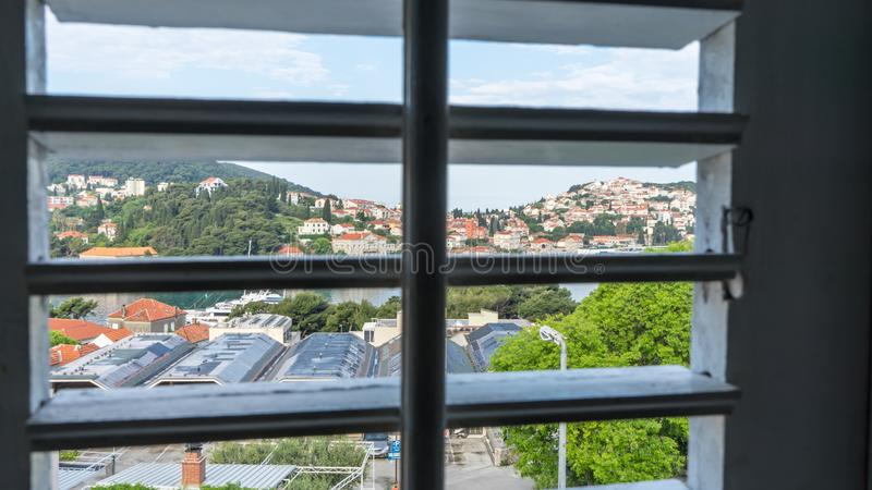 Window view through the blinds. City from inside of the house. Sea town in a hill view from the wooden shutters. Abstract, interior, detail, light, background stock images