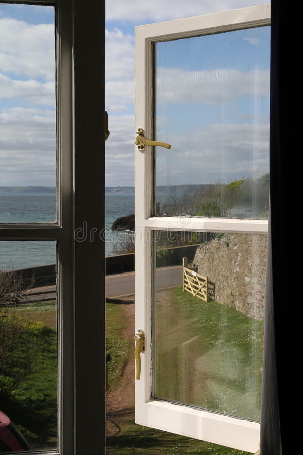 Window view of Hope Cove in Devon. Sunny day with window latches and gate in the background. Road and sea to view royalty free stock photo